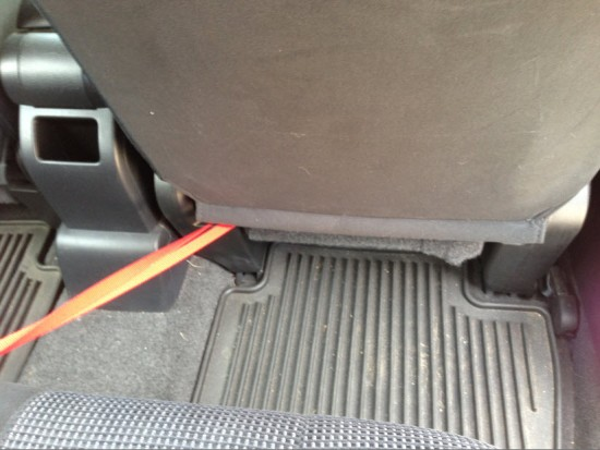 Leashes slip between the passenger seat back, and the bottom of the seat.